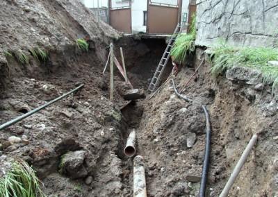 Dům nebyl napojen na kanalizaci. 50m do domu měla být připravena kanalizační přípojka z páteřní kanalizace, umístěné na opačné straně silnice 3,5 metru pod povrchem. Pod branou jsme se výkopem dostali do cca 2,25m hloubky. Na čele výkopu je patrná připravená kanalizační přípojka, v hloubce 75cm. Při rekonstrukcích starých domů není o podobná překvapení nouze…
