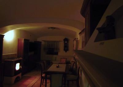 Veškeré světelné zdroje v domě jsou použity LED. Výjimkou budou bodové reflektory pod patami kleneb, jež budou přes stmívače nasvěcovat klenby zespodu. Na fotografii je provizorně na stmívač napojena jedna klasická žárovka. Prostor příjemně osvětluje i oheň z krbu. Výměníkem je teplo rozváděno do topných okruhů. Pro případné přetopení hlavní místnosti jsou připraveny ventilátory i zpětné vzduchovody, zajišťující nucenou cirkulaci teplého vzduchu do pokojů.