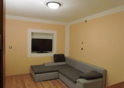 Tentýž pohled nyní. Připravený otvor pod stropem je pro nucenou cirkulaci teplého vzduchu při případném přetopení místnosti s krbem. Tiché ventilátory budou osazeny na opačném konci potrubí. Zpětné potrubí je umístěno skrytě při podlaze. Pokoj na opačné straně domu má stejné přídavné vytápění.